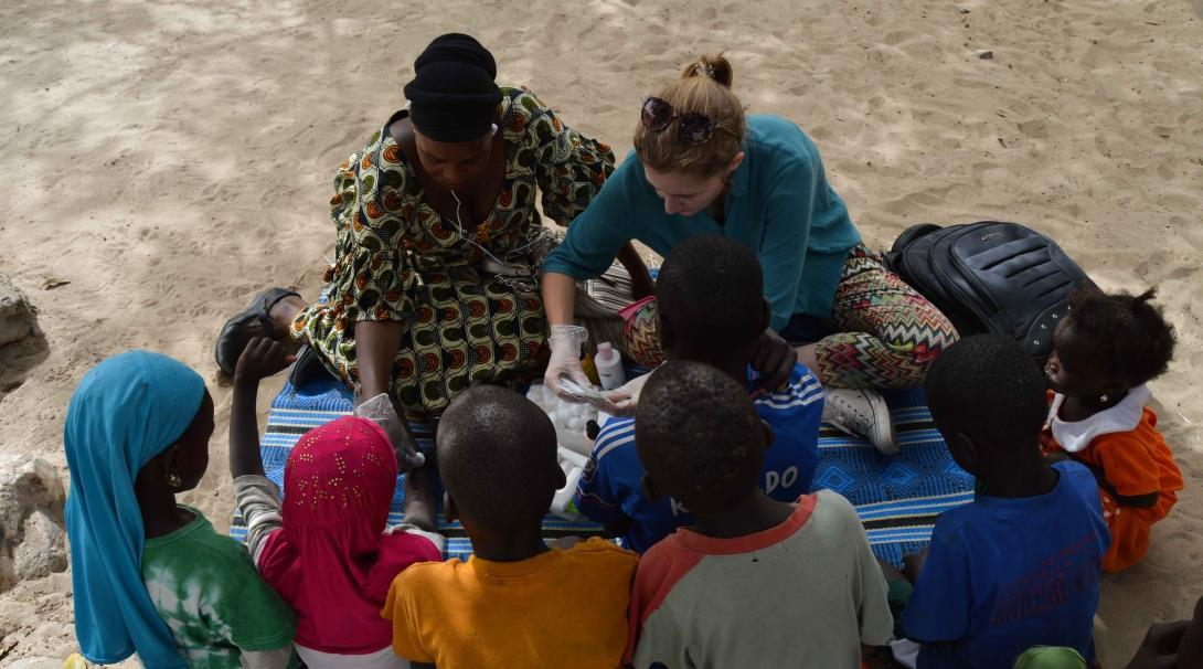 A volunteer with children in Senegal provides medical care during an outreach.